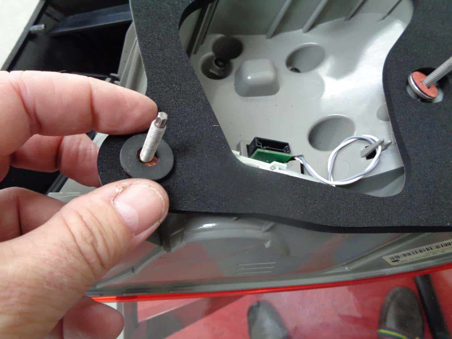 BMW E90 Trunk Leak - install new rubber washer on tail light mounting stud