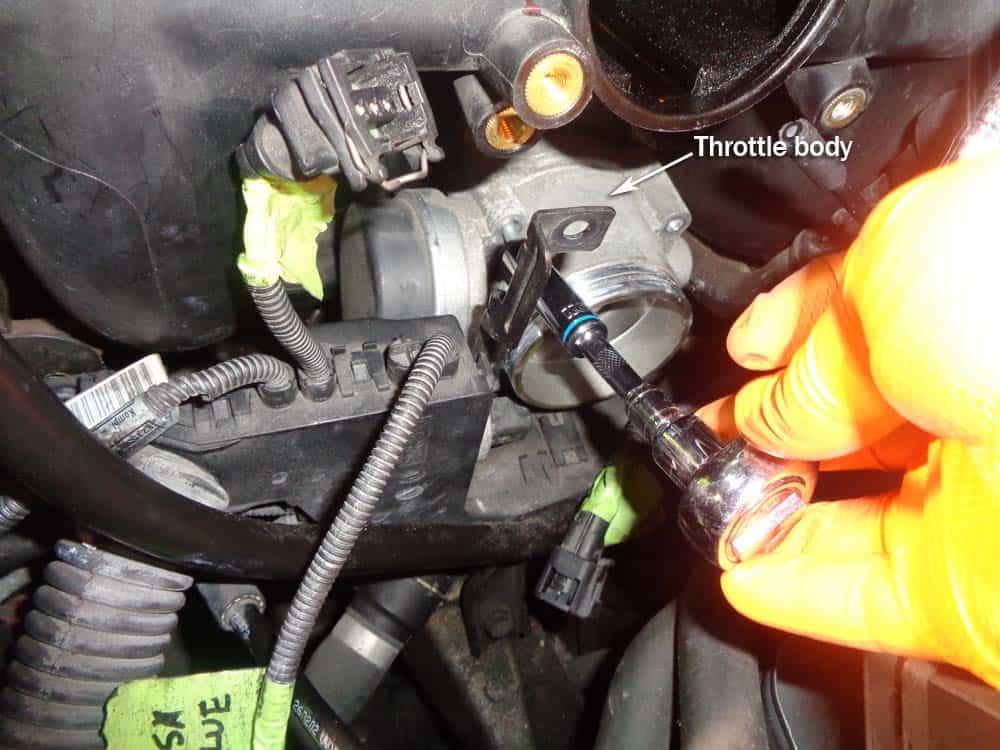 BMW E46 intake manifold - remove the last throttle body bolt and remove the throttle body from the vehicle.