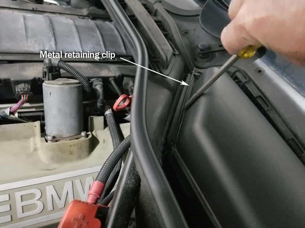 BMW N62 engine tune up - Use a flat blade screwdriver to release the metal retaining clips on the cabin filter containers
