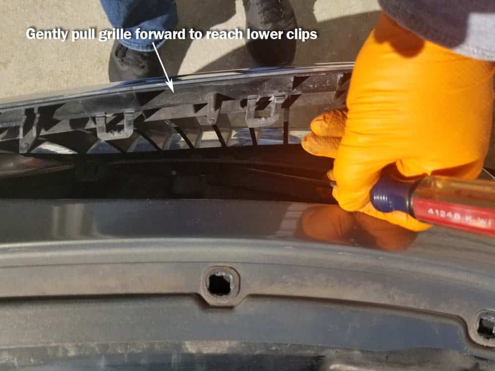 Pull the grille forward to access the lower plastic clips