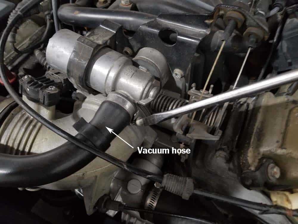Loosen the vacuum hose clamp with a flat blade screwdriver