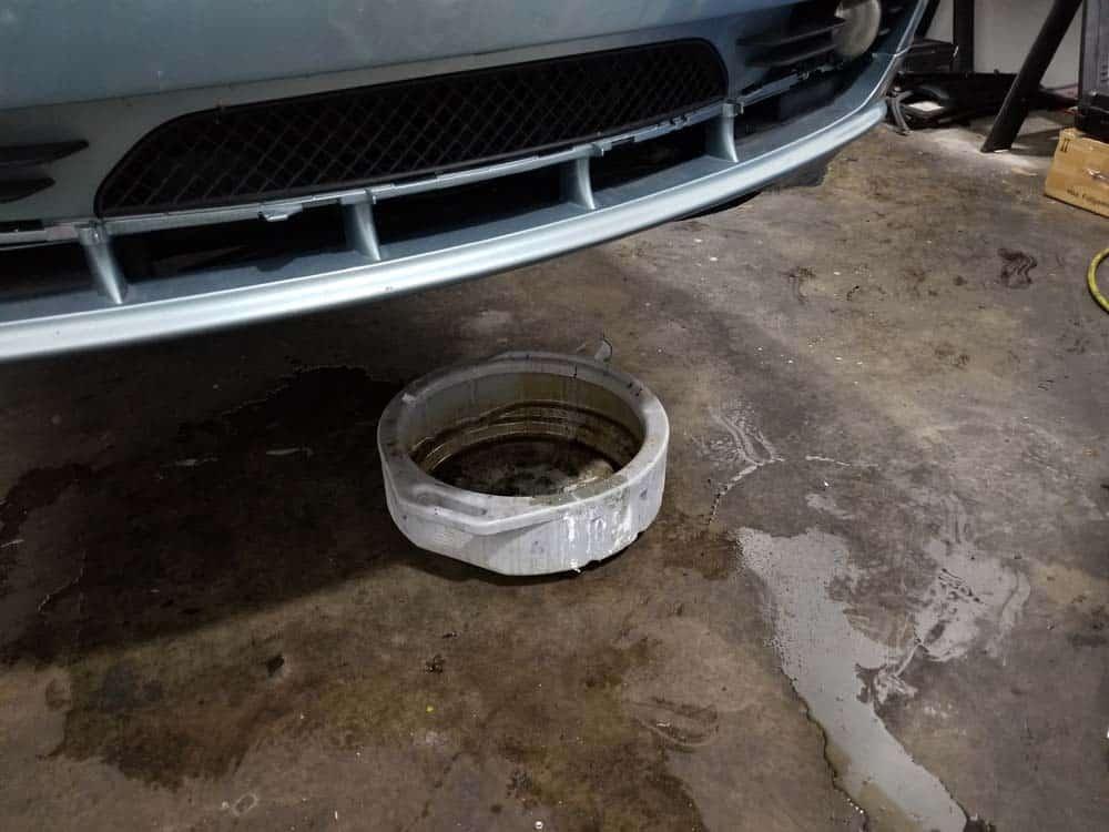 Position a 5 gallon drain pan under the drain plug.