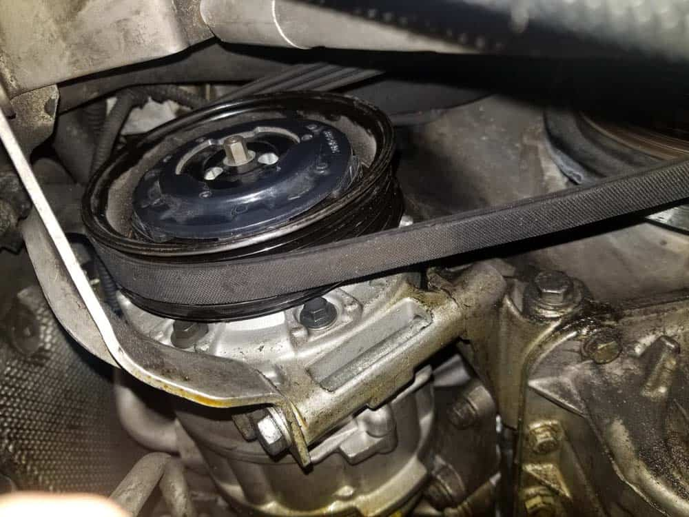 BMW N62 ac belt tensioner - locate the AC belt under the car.