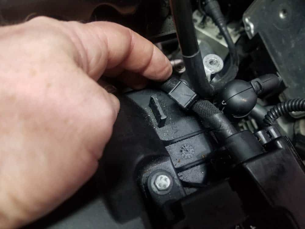 MINI R56 coolant temperature sensor - Unsnap the wiring harness from the rear left corner of the valve cover.