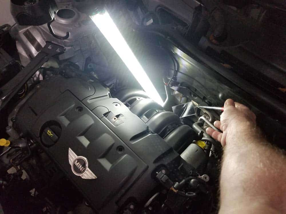 Use a shop light and inspection mirror to find the lower mounting bolt.