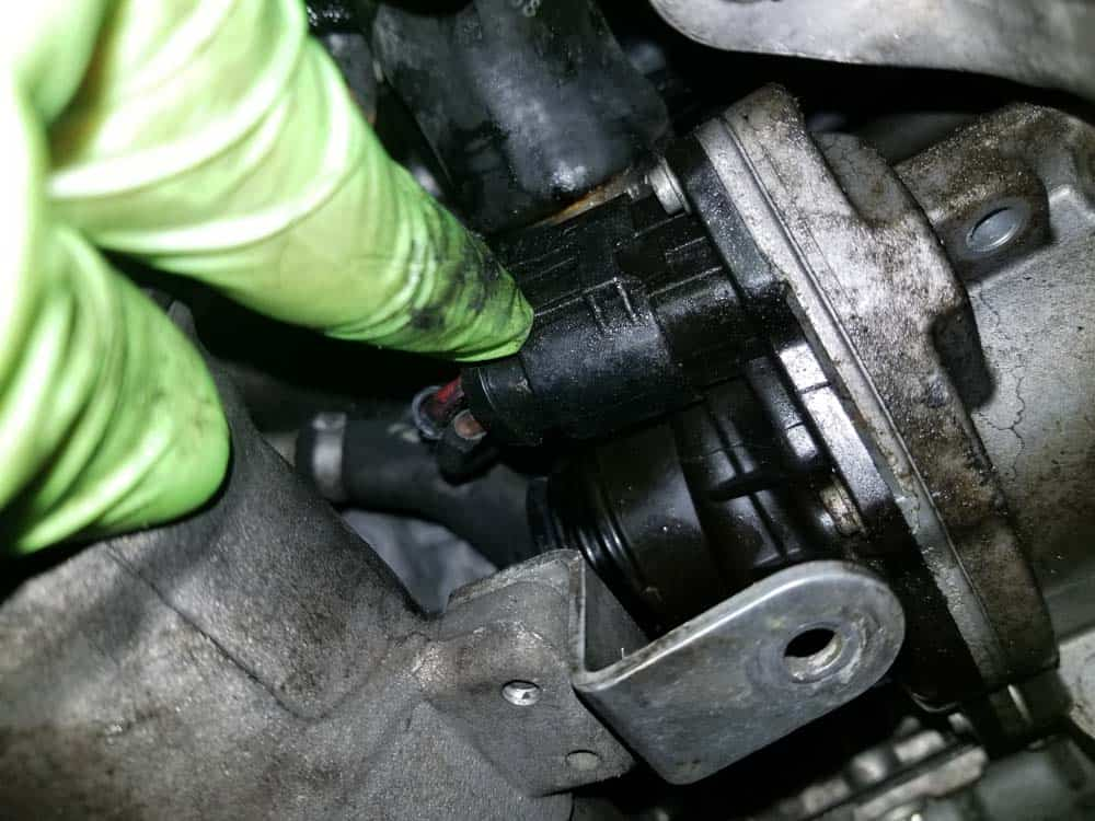 bmw e90 water pump replacement - Depress the plastic locking tab on the water pump's electrical plug