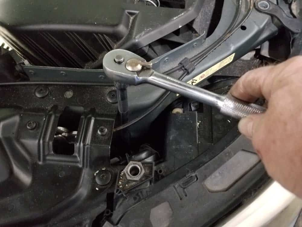 bmw e60 xenon headlight bulb - Use an 8mm socket wrench to loosen the inside lower mounting screw
