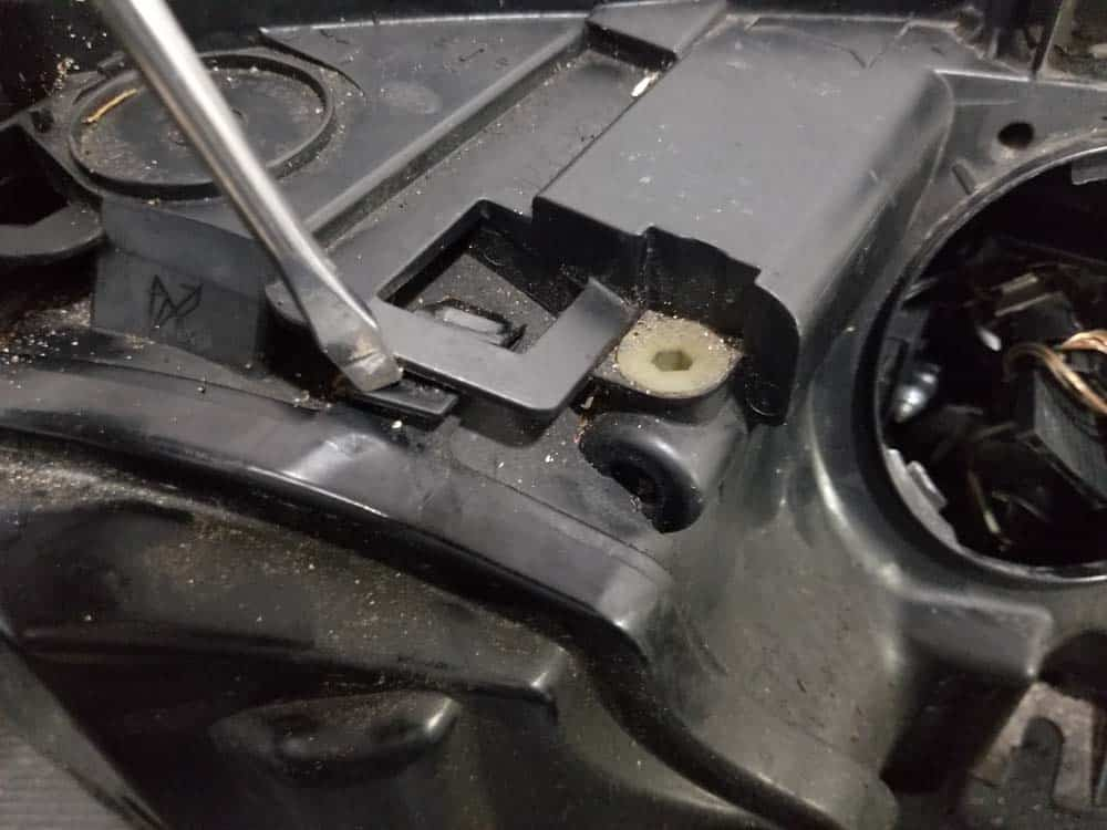 bmw e60 xenon headlight bulb - Use a screwdriver to release the rear bulb cover locking tabs
