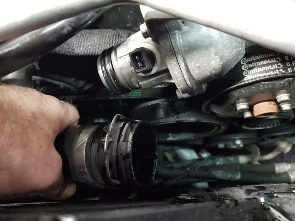Pull the coolant return line free from the thermostat
