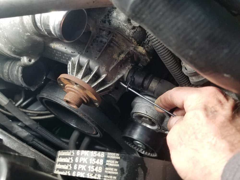 Release the lower coolant return hose from the bottom of the water pump and remove it