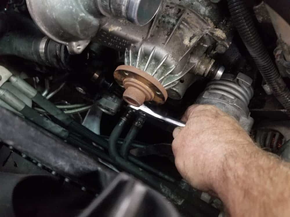 bmw water pump replacement - Remove the lower water pump mounting bolt
