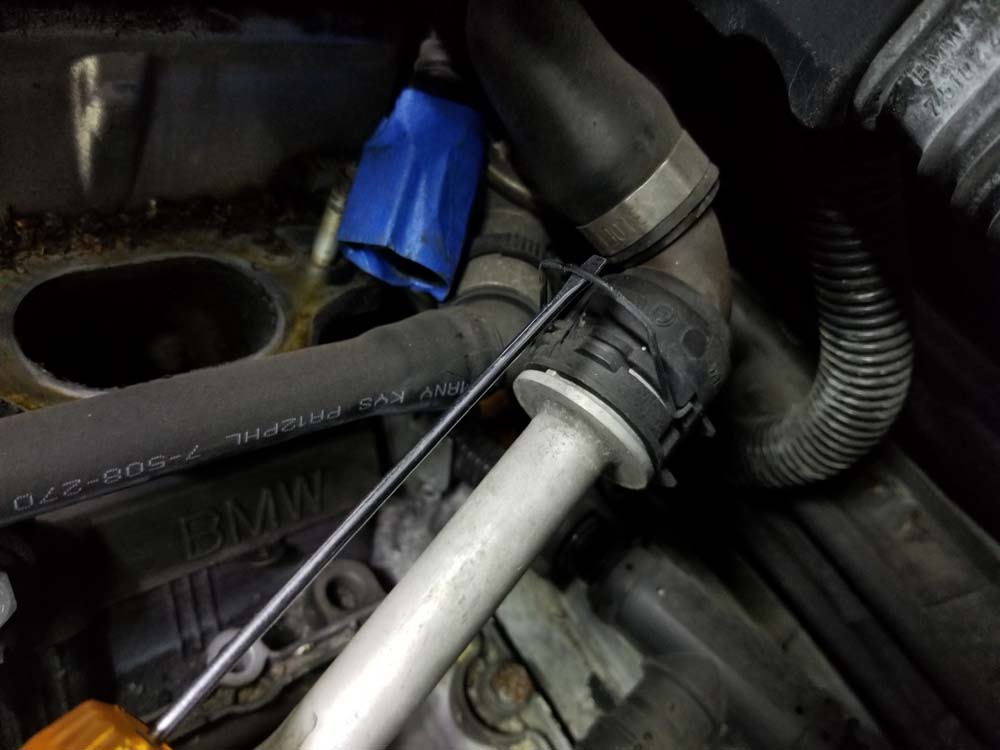 Release the metal locking clip on the heater return line