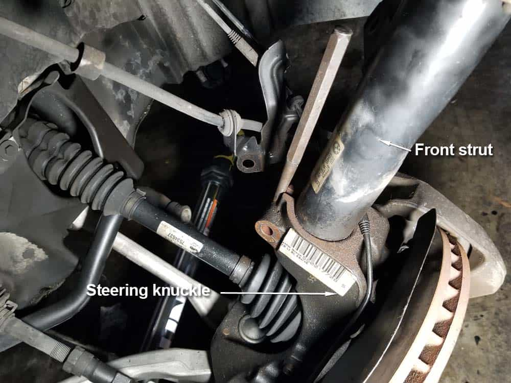 Use a steel punch to spread the steering knuckle open if the strut is seized inside of it.