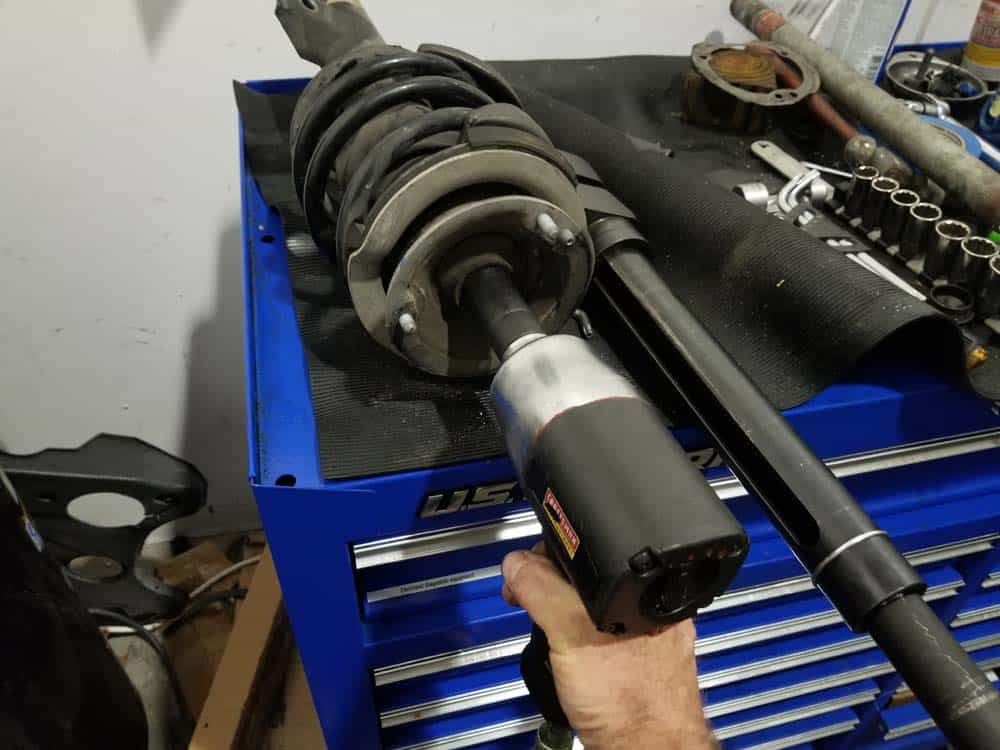 bmw e60 front strut replacement - Use an impact wrench to remove the strut shaft lock nut