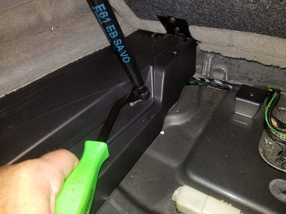 Use a trim removal tool to remove the gas spring from the forward storage compartment