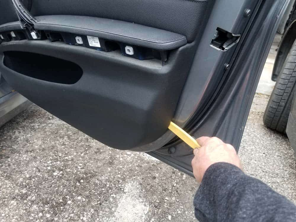 Use a plastic trim removal tool to pry the door panel loose from the frame